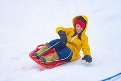 日本女孩滑在节目Yuzawa滑雪场的雪雪撬下 免版税库存照片