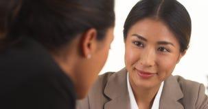 日本女实业家谈话与墨西哥同事 免版税库存照片