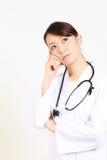 日本女性医生考虑某事 免版税库存照片
