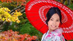 日本妇女在日本庭院里在秋天 图库摄影