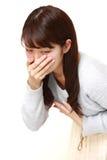 年轻日本妇女感觉象呕吐 库存照片