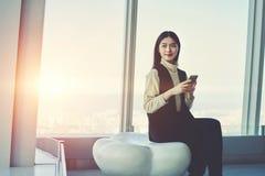 日本妇女成功的企业主检查在手机的电子邮件 免版税库存照片