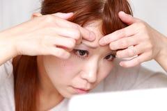 年轻日本妇女担心干燥粗砺的皮肤 库存图片