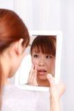 年轻日本妇女担心干燥粗砺的皮肤 免版税库存图片