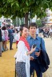 日本妇女游人在传统服装穿戴了在塞维利亚的4月市场 免版税库存图片