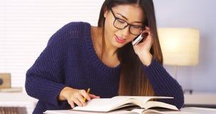 日本妇女谈话在家庭作业帮助的智能手机 库存图片