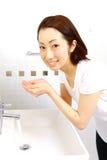 年轻日本妇女洗她的在洗手间的面孔 免版税库存图片