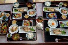 日本居住的时期早餐盘子包括煮熟的白米、烤鱼、煎蛋、豆腐汤、香肠、腌汁、海草等等 免版税库存图片