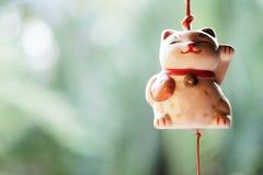 日本幸运的猫玩偶在窗口垂悬 免版税库存图片