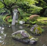 日本庭院的片段有石用青苔盖的灯笼和大岩石的 库存图片