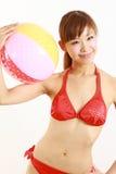 年轻日本有海滩球的妇女佩带的比基尼泳装 库存图片