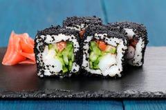 日本染黑tobiko卷用乳脂干酪和黄瓜服务的w 免版税图库摄影