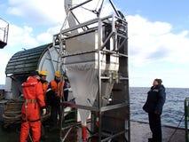 日本海/俄罗斯- 2013年12月01日:Epibenthic爬犁和科学在调查船甲板合作  库存图片