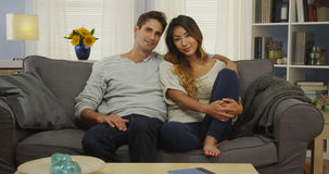日本混杂的夫妇坐长沙发微笑 库存图片