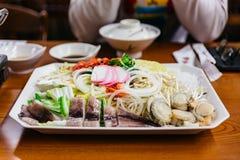 日本热的罐shabu包括乌贼、hotate、虾、鱼丸和菜在餐馆在札幌 北海道,日本 免版税库存照片