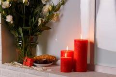 日本玫瑰是白色的在一个花瓶水在蛋糕和新月形面包,在窗台的灼烧的蜡烛旁边 免版税库存图片