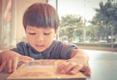 日本男孩有枪阅读书 库存图片