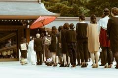 日本神道的信徒的婚礼的队伍在著名明治神宫的在东京,日本 库存照片