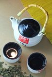 日本茶道、白色瓷茶罐有竹把柄的和象形文字与两个茶杯,绿茶驱散了和叫喊 免版税库存图片