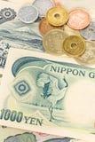 日本金钱日元钞票和硬币 免版税库存图片