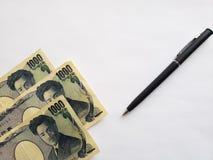 日本钞票、黑笔和白色背景 免版税库存图片