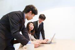 日本队谈论关于互联网内容,看在膝上型计算机个人计算机的显示 库存照片