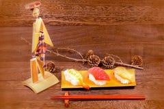 日本食物,与筷子的寿司在木桌上围住backgr 免版税图库摄影