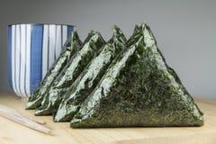 日本食物,米饭团(onigiri)用在蓝色杯子的绿茶 免版税库存照片