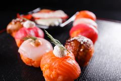 日本食物,鲜美午餐的膳食 海鲜 寿司用鳗鱼,三文鱼,鳟鱼,金枪鱼黑背景 免版税库存照片