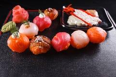 日本食物,鲜美午餐的膳食 海鲜 寿司用鳗鱼,三文鱼,鳟鱼,金枪鱼黑背景 库存图片