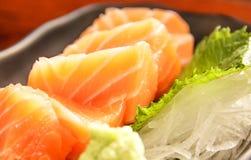 日本食物:三文鱼用在木桌上的被磨碎的白萝卜和薄菏叶子装饰的生鱼片新鲜的未加工的三文鱼肉作为背景 库存图片
