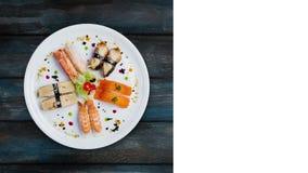 日本食物 在一块白色圆的板材的转动的生鱼片集合,装饰用小花,顶视图 木背景 股票录像