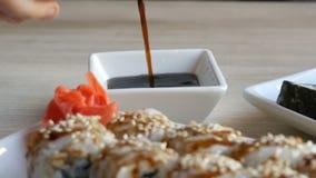 日本食物 寿司卷在桌上说谎在姜山葵和柠檬旁边 酱油从专辑倒 股票录像
