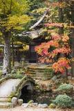 日本高山市Hokke籍有石桥梁秋天的寺庙庭院 免版税库存照片