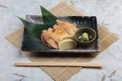 日本鸡烤了与海盐服务用切的柠檬和山葵在石长方形板材有筷子的在makisu 免版税库存图片