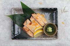日本鸡顶视图烤了与海盐服务用切的柠檬和山葵在石长方形板材在washi 免版税图库摄影