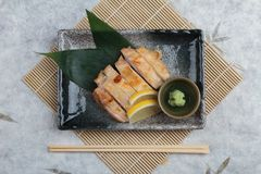 日本鸡顶视图烤了与海盐服务用切的柠檬和山葵在石长方形板材有筷子的 库存照片