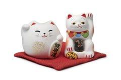 日本maneki neko,在一个红色枕头的幸运的猫 库存照片