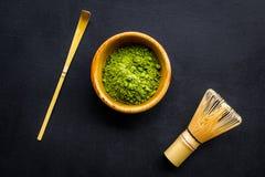 日本matcha茶传统 Matcha辅助部件,在matcha粉末附近的飞奔在黑背景顶视图的碗 库存图片
