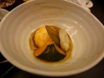 日本ryokan kaiseki晚餐温暖的盘包括甜虾饺子、南瓜、薯类和蜂斗菜在白色陶瓷碗 图库摄影