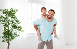 日父亲s 拥抱爸爸和笑的愉快的家庭女儿 免版税库存图片