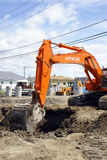 日立橙色挖掘者和深坑 免版税库存照片