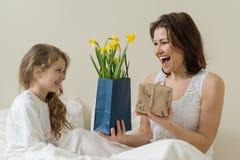 日花产生母亲妈咪儿子 一个愉快的母亲从她的小女儿在床上接受了花束和礼物早晨 库存照片