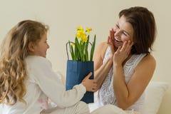 日花产生母亲妈咪儿子 一个愉快的母亲从她的小女儿在床上接受了花束和礼物早晨 免版税库存照片