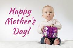 日花产生母亲妈咪儿子 对一些负的严肃的男婴当前在他的胳膊 与礼物的周道的婴儿孩子 准备好明信片 免版税库存照片