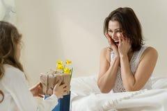 日花产生母亲妈咪儿子 小女儿保留一件礼物和花她的母亲的 卧室,母亲背景内部在床,早晨上 免版税库存图片
