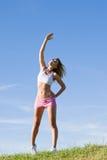 日草甸嬉戏舒展的晴朗的妇女年轻人 免版税库存图片