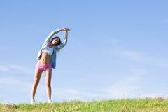 日草甸嬉戏舒展的晴朗的妇女年轻人 免版税图库摄影