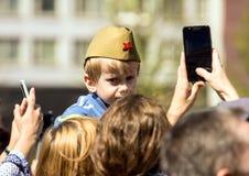日莫斯科胜利 一个军用试验` s盖帽的一个男孩坐他的父亲` s肩膀 图库摄影