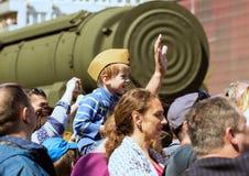 日莫斯科胜利 一个军用试验` s盖帽的一个男孩坐他的父亲` s肩膀 库存照片